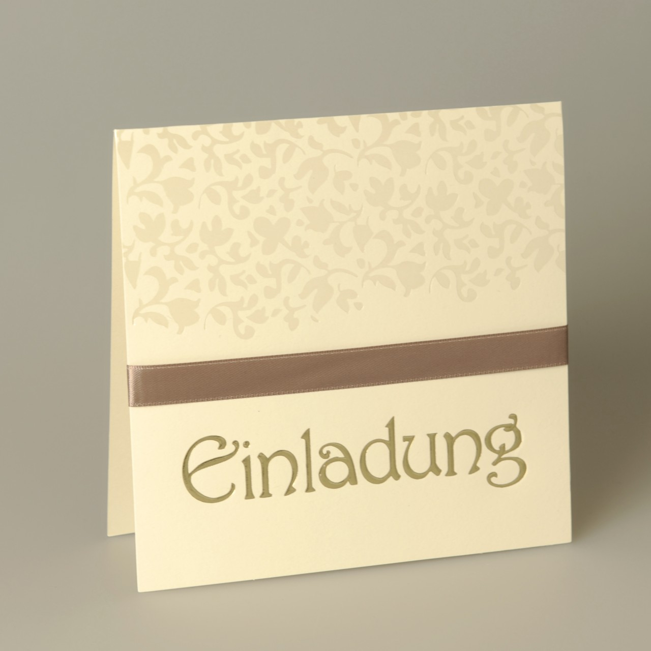 Cremefarbene quadratische Karte mit perlmuttfarbenen Ornamenten, braunem Satinband und Kuvert beige.