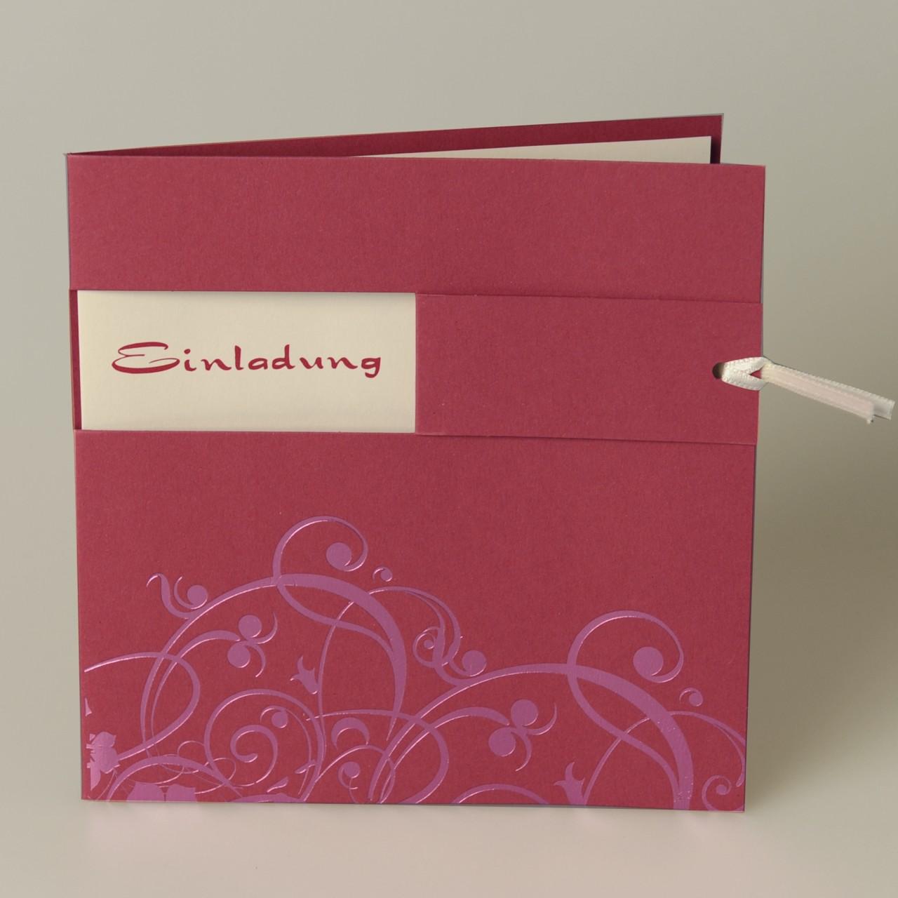 Pinke quadratische Karte mit gedruckten Ornamenten im unterem Bereich der Karte, cremefarbigem Satinband, Einstecker und Kuvert creme.
