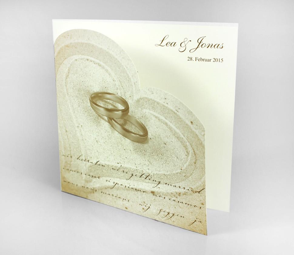 Einladungskarte mit Ringen und Herz im Sand