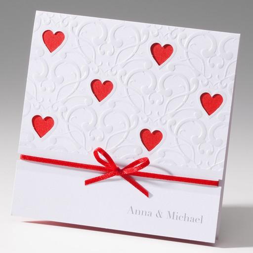 Glänzende weiße Einladungskarte mit gestanzten Herzen und rotem Band