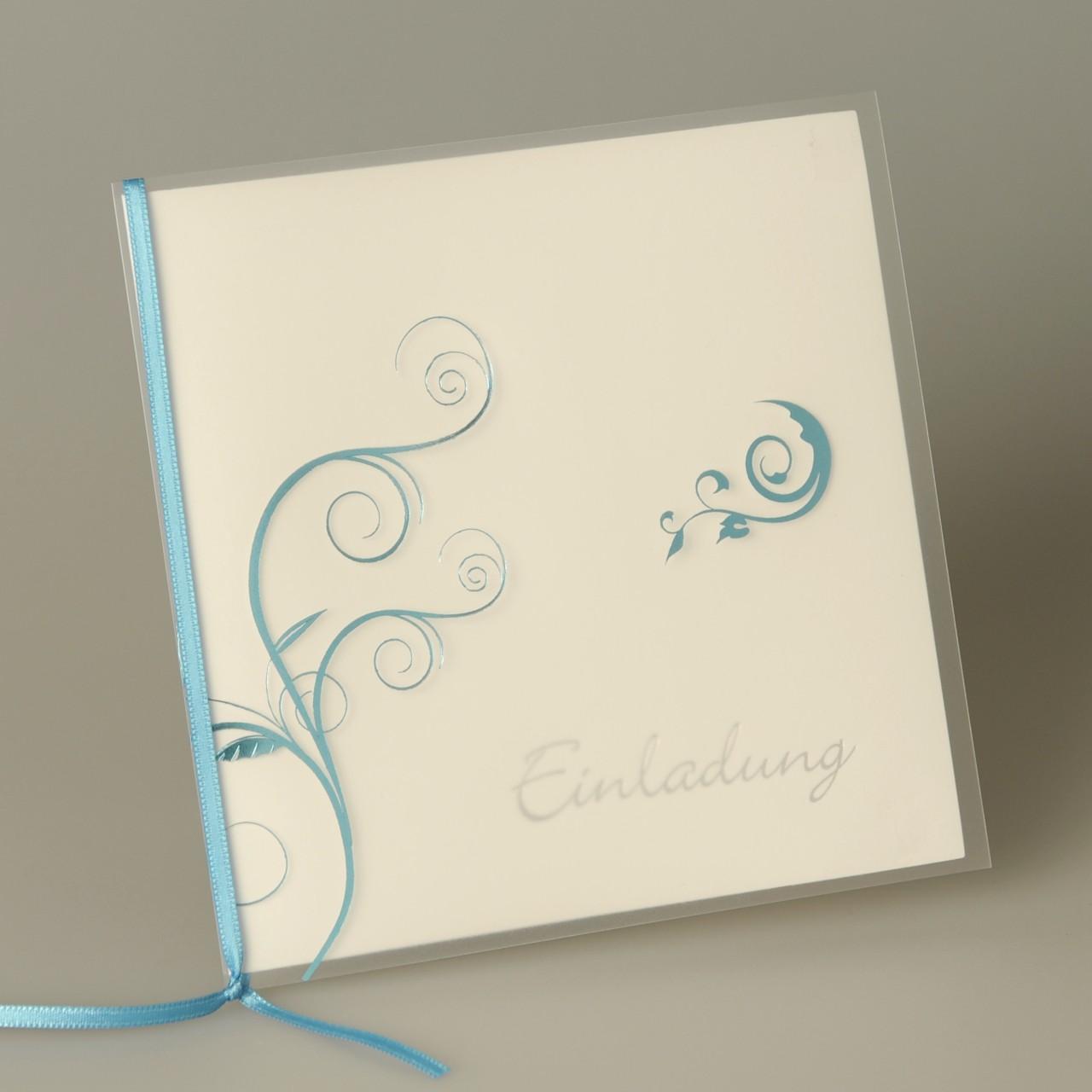 Weiße quadratische Karte mit Kunststoffumschlag, türkisfarbenem Band und weißem Kuvert.