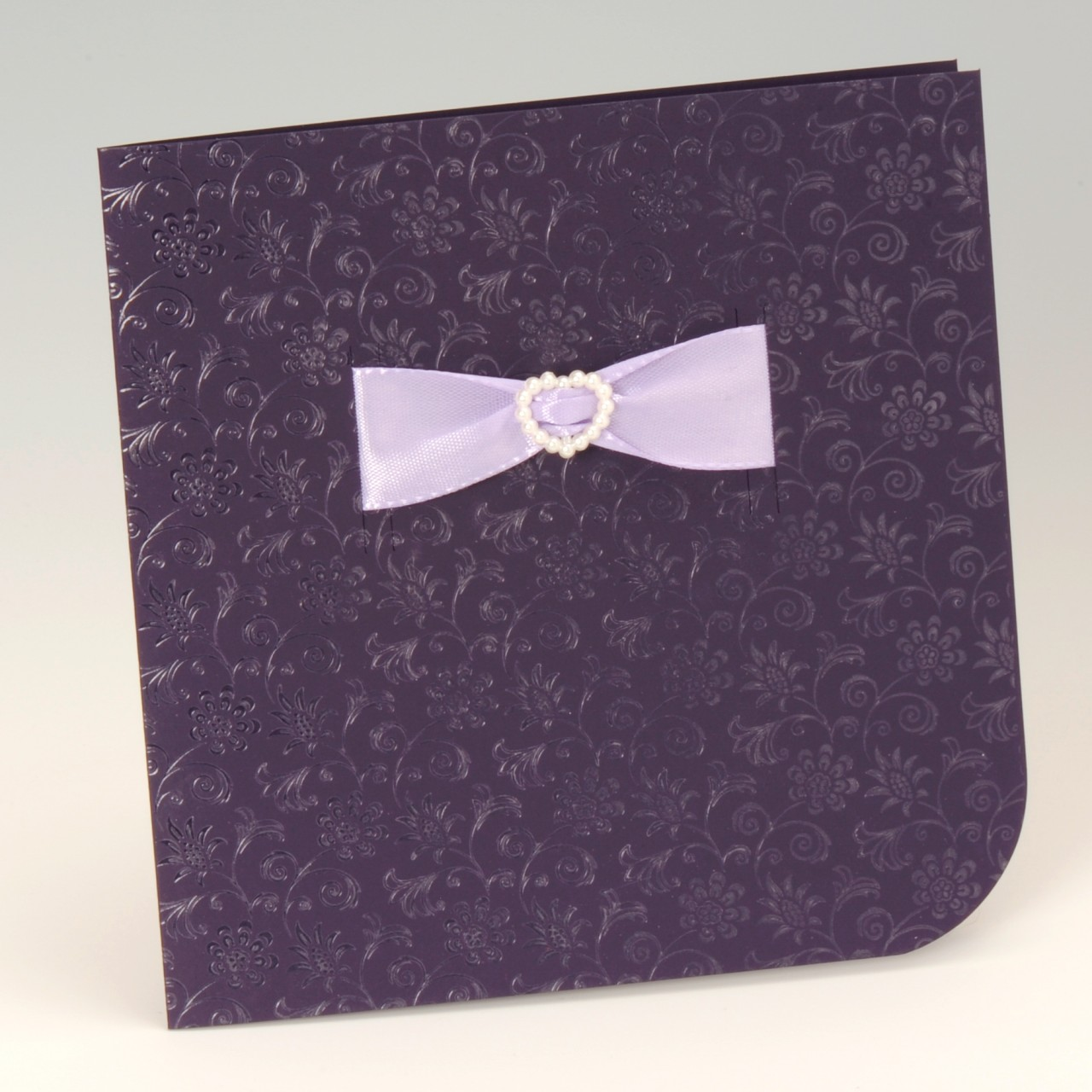 Lilafarbene Einladungskarte mit fliederfarbenem Band und Herz